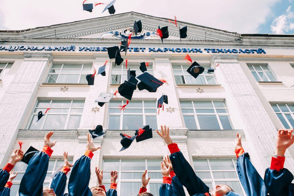 Universitari laureati in un'università russa che lanciano il cappello dopo la proclamazione