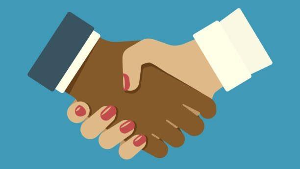 Mano caucasica e mano di colore si stringono in segno di rispetto