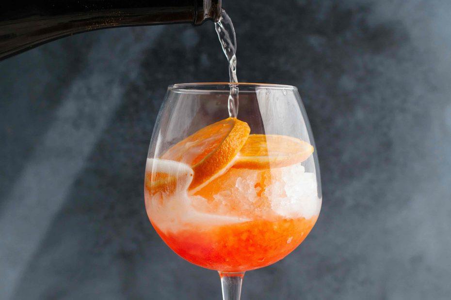 Bottiglia di prosecco che viene versata in un bicchiere per preparare uno Spritz